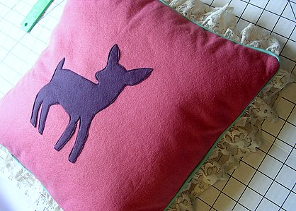 Felt patch stitched onto a pillow using a sewing machine.